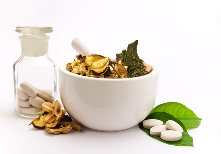 White mortar and pestle. Herbals, pills and green leaves. photo