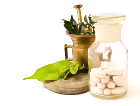 plant drug: Mortar with herbs, and pharmacy bottle. White pills and white background