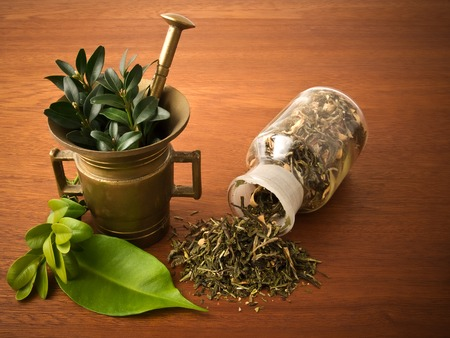 therapeutics: Mortar and pharmacy bottle, with herbs. On the wooden table.