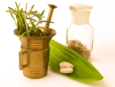 therapeutics: Mortar with herbal. Tablets on the leaf. Stock Photo