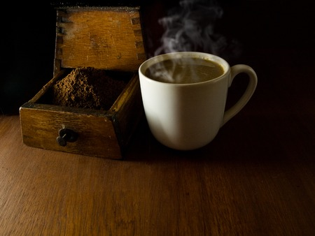 coffeebeans: A cup of hot coffee, and an antique coffee grinder. Wooden table. Stock Photo