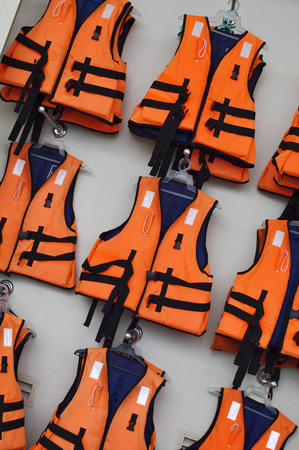 Rows of orange life jackets on the wall, ready for immediate use.