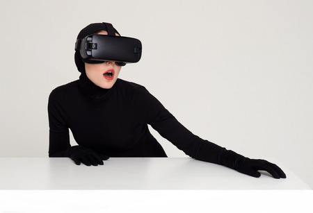catwoman: Woman in black wearing virtual reality glasses sits against white background. Concept: technology, augmented reality.