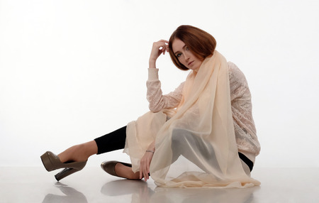 hand on forehead: Young girl in big shawl sits on the floor. Her legs bent at the knees, hand touching a forehead. Black skinny pants, heels, creme scarf, fashion, make-up.
