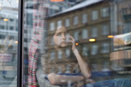 bowed head: Young girl waiting in cafe for someone, who late. Her fingers near chin, head bowed. The window displays the old house and office building. City life, window reflection