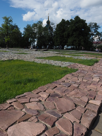 The foundation of theThe Church of the Tithes or Church of the Dormition of the Virgin, Kiev, Ukraine in the backlight. Running Man. Sun, rays, sky, clouds. Tourist attraction. Andriyivskyy Descent.