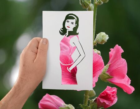 A hand holds a paper stencil of young long-haired girl against background of pink flowers.The contours of beautiful woman in pink dress. Fashion, glamour. Dress making.