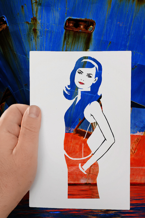 longhaired: A hand holds a paper stencil of young long-haired girl against background ofblue red boat. The contours of beautiful woman in red blue dress. Fashion, glamour. Dress making.
