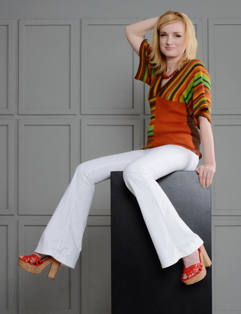 chear: Beautiful girl posing in studio near small chear in 1970s clothes. She is dressed in a striped knitted blouse and crocheted white jeans, high heels. Her leg bent in the knee