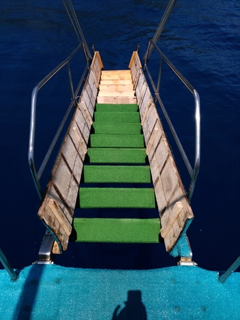 The gangway is green steps leading to the sea. Yacht, blue - blue water, sea. Travel - water transport in motion. Stock Photo