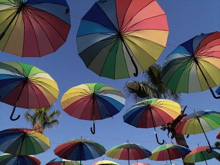 Multicolored umbrellas against the sky in the backlight. Decorative canopy, red, blue green, yellow. Colors of rainbow. The art of street decor, the atmosphere of a holiday, summer, rest, rain is not a hindrance
