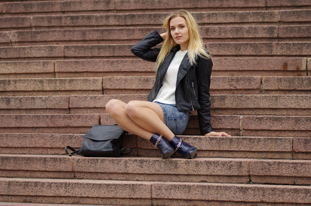 A beautiful blonde woman in a denim (jeans) skirt above the knee, white cardigan, black leather jacket, boots, sits on the steps of stone staircase. Near black bag. Street fashion, casual style