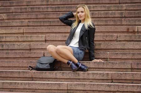 Een mooie blonde vrouw in een denim (jeans) rok boven de knie, wit vest, zwart leren jack, laarzen, zit op de trappen van een stenen trap. Dichtbij zwarte tas. Streetmode, casual stijl