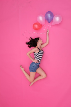 A black-haired girl flying on inflatable balls on a pink background. Romantic story, fabulous flight, jeans (denim) shorts, striped T-shirt (vest), pink background, flat lay, fun, colorful world