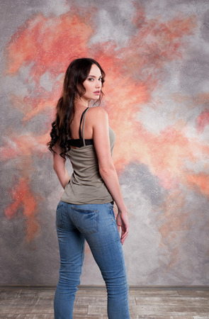 Pretty girl at studio photo shoot. Standing in a back view pose. Showing emotions and play. Indoor fashion photography. Stock Photo - 89180771
