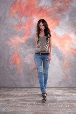 Beautiful young female walking in studio. Posing in movement, wearing jeans and t-shirt. Model look and fashion show style.