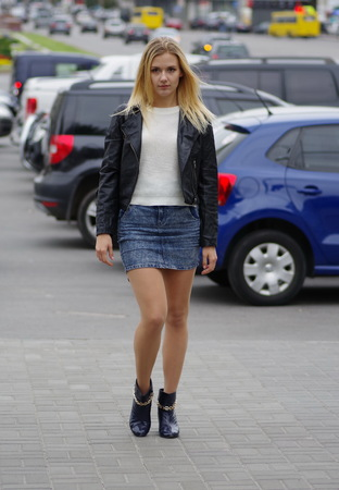 Pretty blonde girl is walking in a street, wearing short jeans skirt, white sweater and black leather coat. Stock Photo