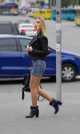 Pretty blonde girl is walking in a street. She is looking to her left. She is wearing short jeans skirt, white sweater and black leather coat. Stock Photo