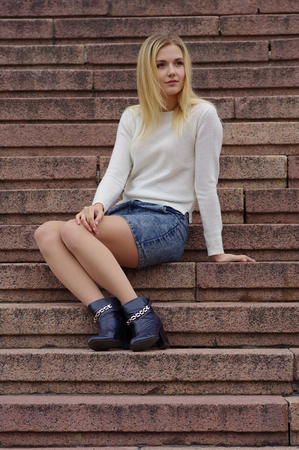 The blond girl is sitting on the street steps. Jeans skirt and white knitted sweater. Thoughtful look. Street fashion.