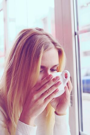 Portrait of a beautiful blonde girl in a white knitted sweater drinking tea. A white cup of tea warms the girls hands. An outdoor cafe. Stock Photo