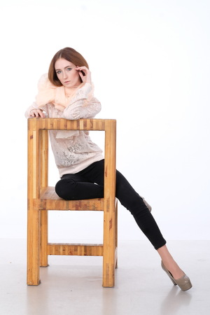 The red-haired girl is playfully posing in a lace blouse and a translucent scarf sitting on a wooden chair. Her legs are bent at the knees, Hands - on the elbows. Grace, thoughtfulness