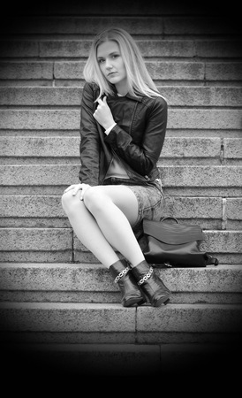 Pretty young girl is sitting on a marble stairs. Her handbag is near her legs. Wearing jeans skirt, black leather coat. She has nice long blonde hair.