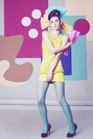 Female model in yellow is actively posing in the studio on an unusual background. Fashion story, Danish - Japanise design. Color composition. Eccentric attire. Short dress, high heels. Blue pantyhose Stock Photo