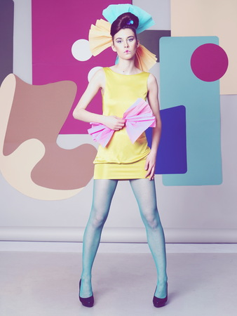 Female model in yellow is actively posing in the studio on an unusual background. Banque d'images