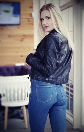 Beautiful young blonde woman posing in cafe. She wears a black leather jacket and blue jeans. Large bright windows in the cafe. Sexual pose, jeans, backside 스톡 콘텐츠