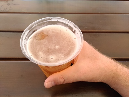 Man's hand holding plastic glass with beer against blurred seascape and Street exterior