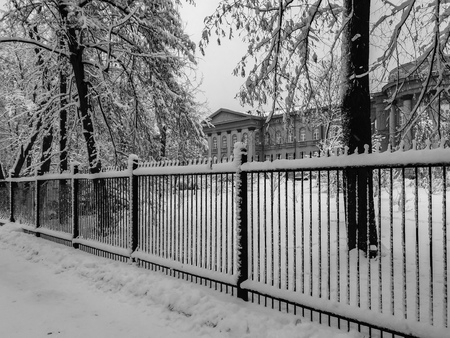 Winter, snow, red painted building of Kiev university snow-covered, view from botanic garden park side, black and white photography