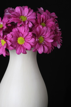 bouquet of magenta with yellow flowers in vase isolated on black
