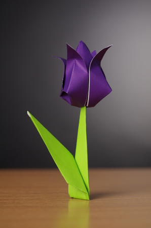 Origami tulip, isolated on table, two paper colors, violet and green 免版税图像