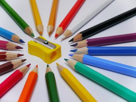 Lápices de colores aislados sobre fondo blanco con sacapuntas amarillo