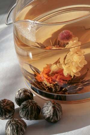 A glass teapot filled with boiling water and brewed flower tea from China. A flower ball blooms nearby. There are balls showing how this tea looks like during transportation. Reklamní fotografie - 116373913