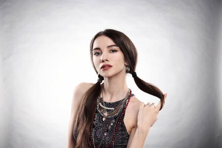 """Portrait of a girl in a dress in the style of the sixties - seventies sitting pose in a studio about neck jewelery beads blouse hairstyle """"pigtail"""""""