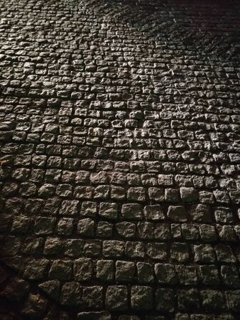 alter Steinhintergrund, Straße, Kopfsteinpflasterstraße in Autolichtern, harte Beleuchtung, schräge Strahlen, Lichtflecken