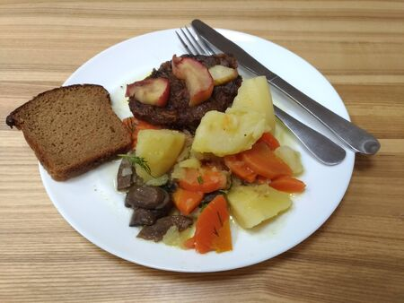 stewed potatoes with vegetables, beef liver with apples, fork metal knife