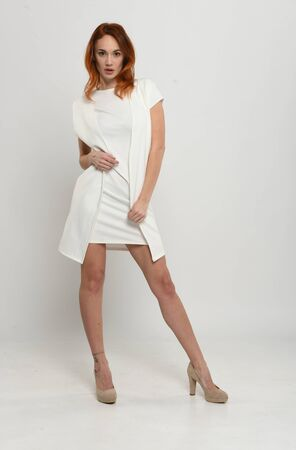 Beautiful redhead girl in a short light beige dress demonstrates a model pose on an isolated neutral Light background. Fashion, modern clothes and style.