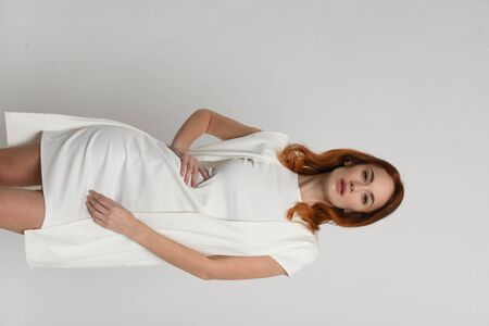 Portrait of beautiful woman with red hair in a beige-white dress in model pose on neutral light background. Space for text, isolated figure, fashion model. Фото со стока