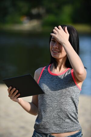 young girl with a tablet in a resting place in sunny weather Imagens