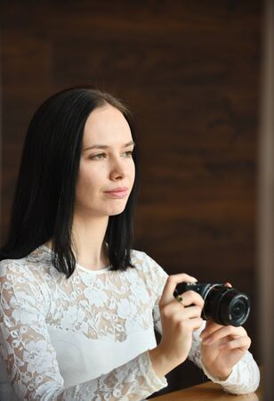 Young brunette woman, novice photographer, with modern compact digital camera takes pichures