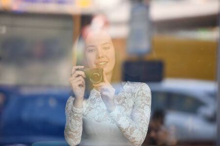 A female amateur photographer with a compact digital camera in a public place is shooting. View through glass, street reflection, office cafe