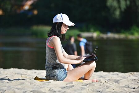 Woman with a tablet at beach sitting in t-shirt and sexy denim shorts on sand and looking at screen.