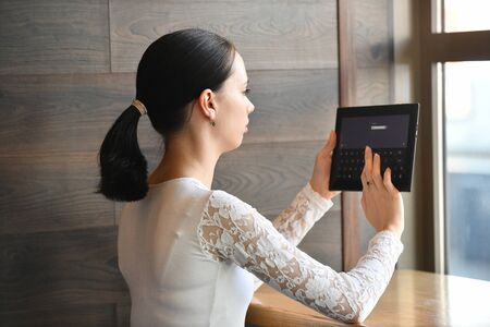 girl works in a cafe with a tablet, enters a password, hairstyle tail, against the background of a window Stockfoto