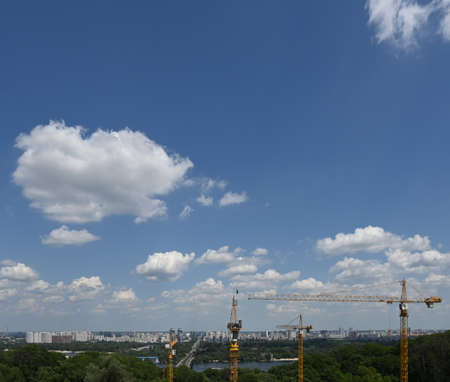 Clouds over the city on a summer day, construction cranes. Panorama of Kiev