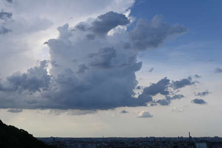 Expressive clouds in the sky in dry summer weather over city, volumetric clouds, blue sky. Stockfoto