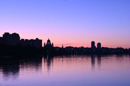 Panorama of Kiev in the area of obolonskaya embankment at sunset in summer, cityscape at blue hour with beautiful crimson-blue shades of the sky, Svyato-Pokrovskiy sobor - Holy Protection Cathedral Stockfoto