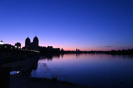 Panorama of Kiev in the area of obolonskaya embankment at sunset in summer, cityscape at blue hour with beautiful crimson-blue shades of the sky