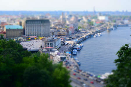 Summer panorama of the city with the effect of miniature, small figures of people, trees, city lit by the sun, narrow depth of field, as if a toy picture. Kiev view of Postal Square from top hills. Stockfoto